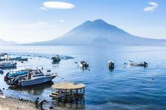 Moored boats, beach & volcanoes, Lake Atitlan, Guatemala stock photography