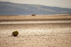 A moored buoy on an empty beach, on a sunny afternoon. West Kirby beach UK. With a view of the beach, the Welsh hills are in the far distance stock photography