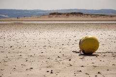 A moored buoy on an empty beach, on a sunny afternoon. West Kirby beach UK. With a view of Hilbre Island Nature Reserve, and the Welsh hills are in the far stock photos