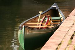Moored canoe and lifevest. A moored canoe with life jacket and paddles Stock Photography
