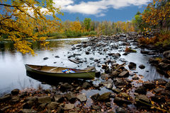 Moored Canoe in a Northern Stream. A canoe sits moored on a tranquil stream durrounded by fall colours Royalty Free Stock Image