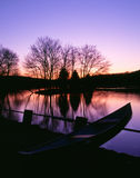 Moored Canoe by a Twilight Lake. This canoe rests peacefully on the shore of a beautiful lake at twilight stock photography