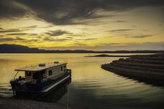 Moored houseboat at dusk. A houseboat moored to a muddy shore in Lake Mead at dusk, Nevada Stock Photos
