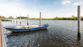 Moored iron rowing boat in rippling water Royalty Free Stock Photography