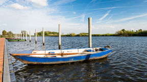 Moored iron rowing boat in rippling water Stock Images