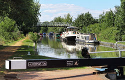 Moored Narrowboats on an English Canal. Narrowboats moored on the Kennett and Avon Canal in England with footbridge in the background Stock Photo