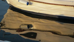 Moored rowing boat on the background of waves close-up