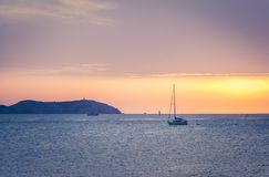Moored sailboat at the coast of Ibiza in sunset. Sunset with a Sailing boat over mediterranean sea water in Ibiza, Spain Stock Photo