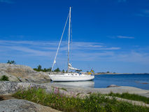 Moored sailboat at small archipelago island in the sun Stock Photos