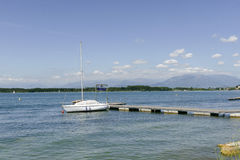 Moored sailboat and small pier on Viverone lake, Italy Stock Image