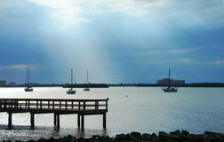 Moored sailboats in calm bay with dramatic clouds sun rays Stock Image