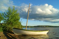 Moored skiff. Wooden skiff with a deflated sail, moored on the unequipped shore of the lake Stock Photos