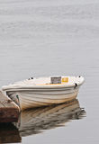 Moored small boat to a wood dock. In a back bay of an isolated berried island stock images