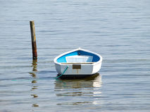 Moored small dingy rowing boat. On still calm water stock photography