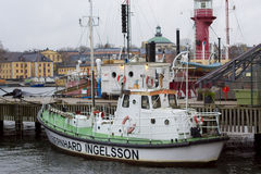 Moored in Stockholm berth tug. Marine tractor white with the name Bernhard Ingelsson parked in Stockholm Harbor at the pier in November 2013. In the background Stock Photography