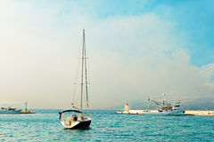 Moored yacht and a fishing trawler in the harbor of a small town called Postira - Croatia, island Brac Royalty Free Stock Photos