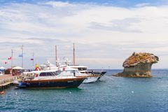 Moored yachts near Il Fungo, Ischia. Lacco Ameno, Italy - August 11, 2015:  Moored yachts with passengers on board near Il Fungo natural landmark. Mushroom Royalty Free Stock Image