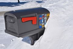 USPS mailbox buried in the snow. MOORHEAD, MIINNESOTA, February 13, 2019: A mailbox buried in a snowdrift displays house numbers with old license plate numbers stock photography