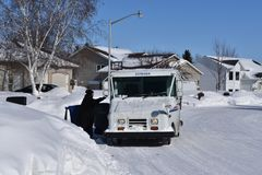 Mail carrier delivers mail for the USPS. MOORHEAD, MINNESOTA, February15, 2019: The mail carrier delivers daily mail in a snow covered neighborhood with a royalty free stock photo