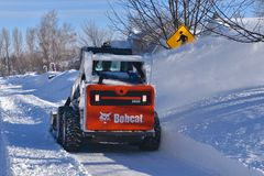 Bobcat Skid steer blows snow after a storm. MOORHEAD, MINNESOTA, March 9, 2019: The S650 Bobcat skid steer removing driveway snow is headquartered in West Fargo stock photography