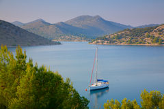 Mooring. Sailboat on a mooring ball in a quiet harbor between the islands off the coast of Croatia royalty free stock photography
