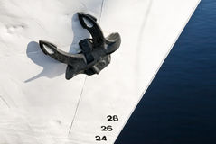 Mooring anchor. Close up of a black ship's mooring anchor on white painted bow with draft scale numbering Royalty Free Stock Photo