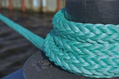 Mooring bollard. With nautical rope knotted on it stock photo