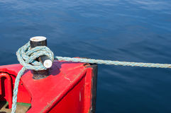 Mooring bollard with blue rope in marina. Stock Photo