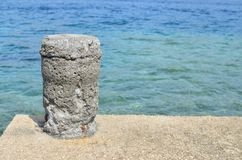 Mooring bollard on a dock. Mooring bollard on a sea dock against blue sea water Royalty Free Stock Photo