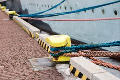 A mooring bollard entwined with a mooring rope. Moored ships at. The port quay. Season winter stock image