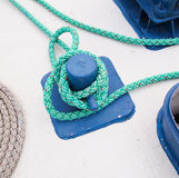 Mooring bollard with green rope. Close-up of mooring bollard with green rope in marina Stock Images
