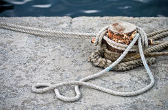 Mooring bollard with knotted nautical ropes. Closeup photo of an old rusted mooring bollard with knotted nautical ropes Royalty Free Stock Photos
