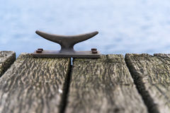 Mooring bollard of metal on a wooden pier bridge at the sea, cop. Y space, detail with selected focus and narrow depth of field royalty free stock photos