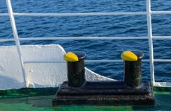 Mooring bollard paint in black and yellow. Detail of old passenger ship with mooring bollard, fence and rippled sea in the background stock photos