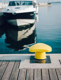 Mooring bollard on a pier. Mooring bollard on a wooden pier with docked luxury yacht on the background Royalty Free Stock Image