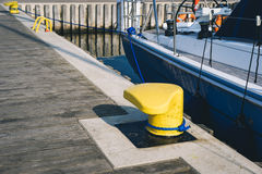 Mooring bollard on a pier. Mooring bollard on a wooden pier with docked luxury yacht on the background Royalty Free Stock Photography