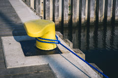 Mooring bollard on a pier. Yellow mooring bollard on a wooden pier with morring line Royalty Free Stock Photo
