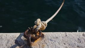 Mooring bollard and rope attached to a rusty metal mesh.  stock footage