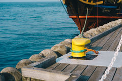 Mooring bollard on a wooden pier. With docked pirate ship on the background Stock Image
