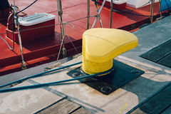 Mooring bollard on a wooden pier. With docked red boat on the background Stock Photos