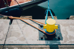 Mooring bollard on a wooden pier. Yellow mooring bollard on a wooden pier with docked boat on the background Stock Photos