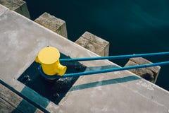 Mooring bollard on a wooden pier. Yellow mooring bollard on wooden pier with mooring rope royalty free stock photo