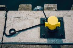 Mooring bollard on a wooden pier. Yellow mooring bollard on pier with mooring ropes stock photos