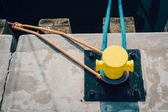 Mooring bollard on a wooden pier. Yellow mooring bollard on pier with mooring ropes stock image