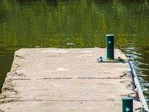Mooring bollards on the catwalk of the river port in Veseli nad Moravou. Match with the acid greenish colour of the water stock images