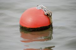 Mooring Buoy. A bright orange mooring buoy floating in the waters of a marina Stock Images