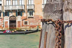 Mooring chain. Close up of Venetian mooring post on the grand canal in Venice with out of focus gondola in the background royalty free stock images
