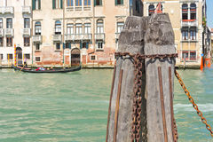 Mooring chain. Close up of Venetian mooring post on the grand canal in Venice with out of focus gondola in the background royalty free stock photography