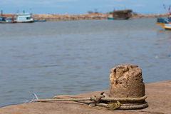A mooring on a dock in a port keeps an old fishing trawler tethered Royalty Free Stock Photos