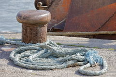 Mooring at the dock. Ropes connected to mooring at the dock Royalty Free Stock Photography